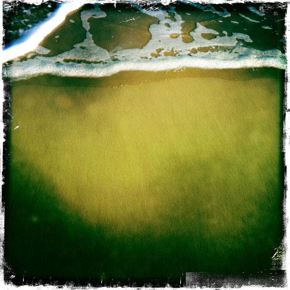 Ebb Tide - sea foam on the beach